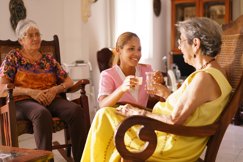 Old people in geriatric hospice: young attractive hispanic woman working as nurse helps a senior woman. She gives a water glass and prescription medicine to the aged patient