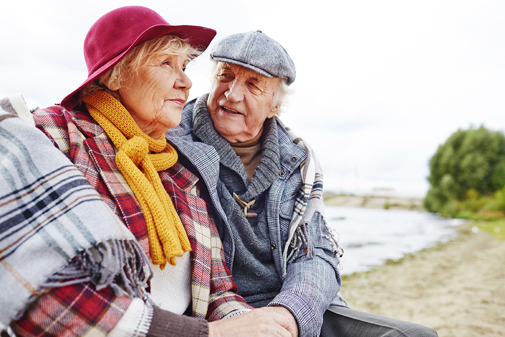 Retired couple in warm clothes having outdoor rest