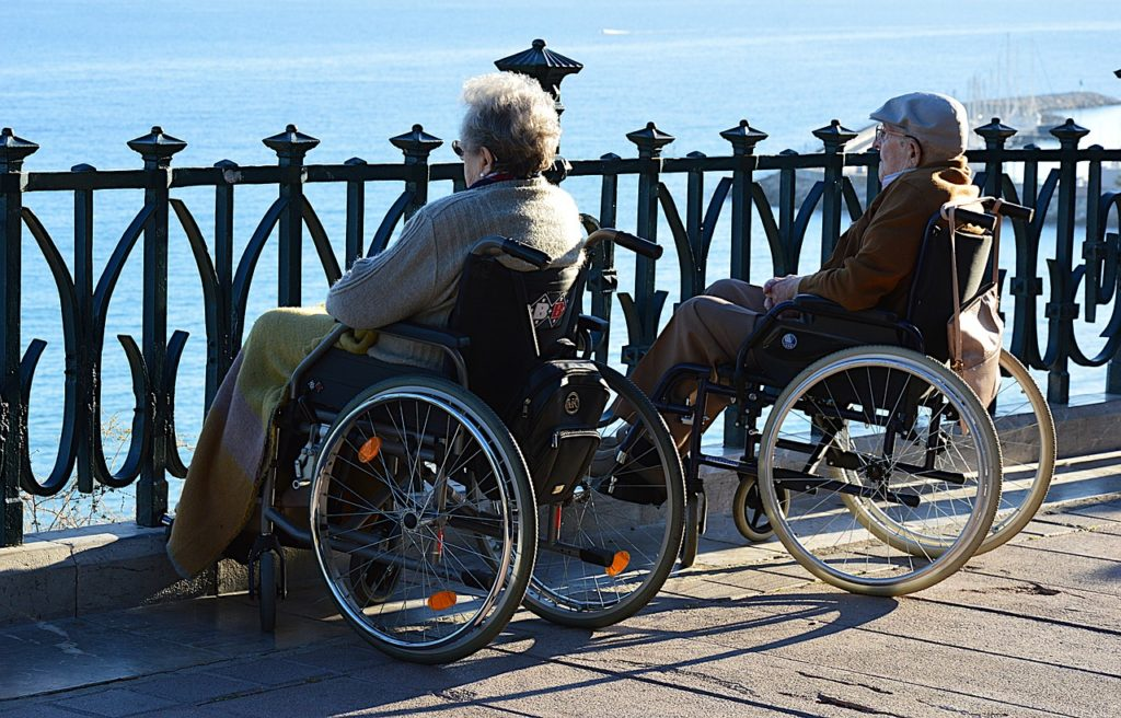 An elderly couple in wheelchairs looking out at the sea