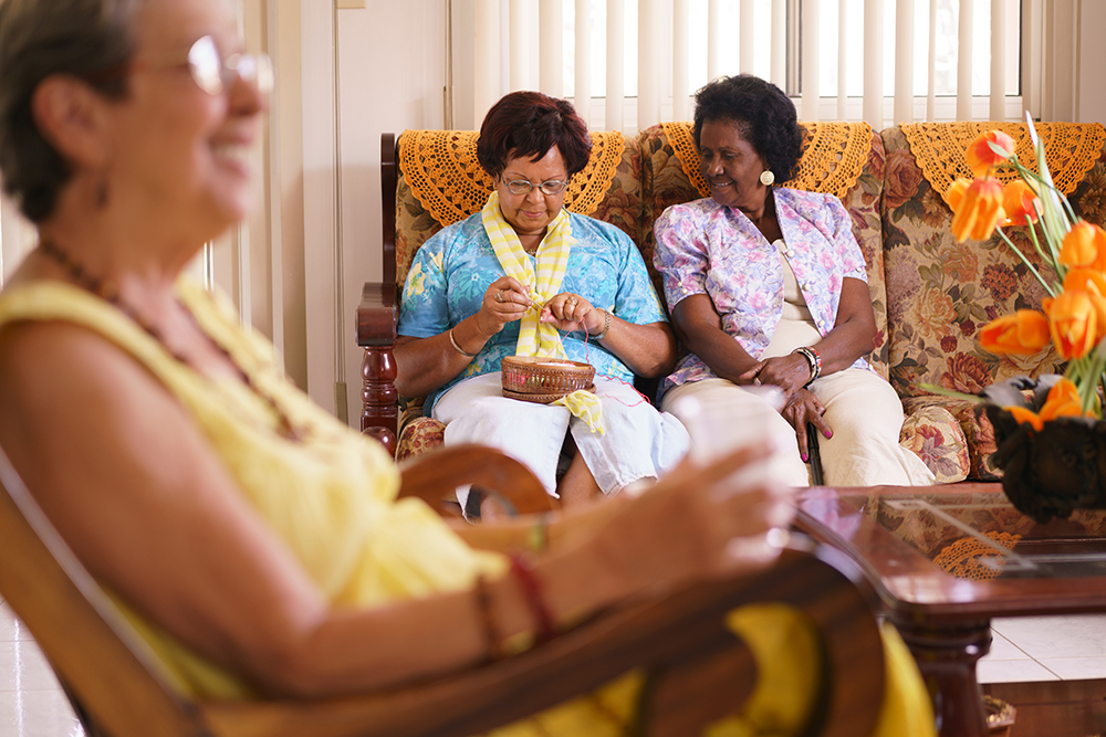 Old people in geriatric hospice: Senior woman sitting on sofa in hospital, knitting with ball of wool between other ladies. The aged grandma is pensive and focused on her hobby.