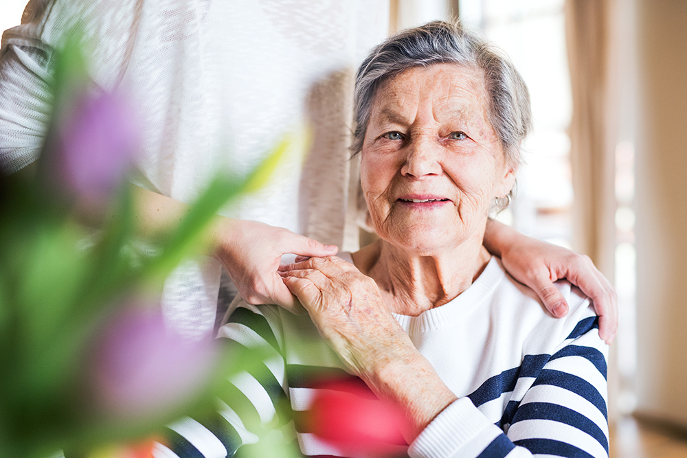 Portrait of an elderly grandmother with an unrecognizable adult granddaughter at home.