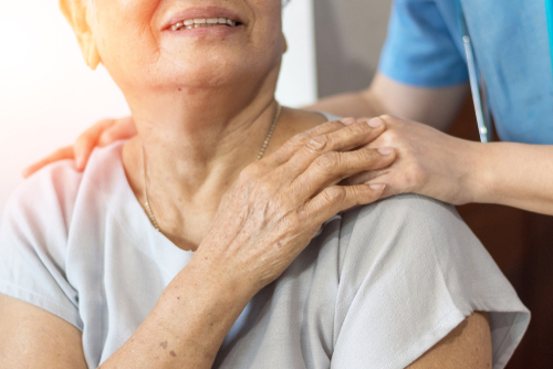 An elderly woman with a younger care giver's hand on her shoulder - What is Pain Management?
