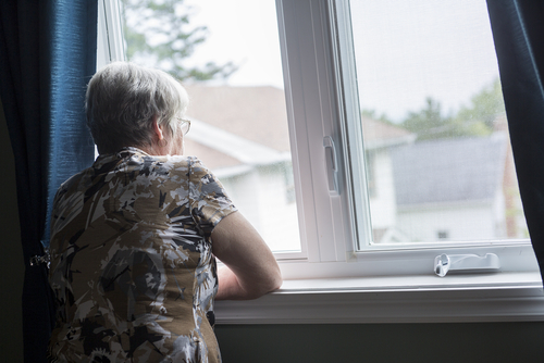 A senior living alone, looking out a window.
