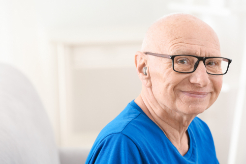 A man with a hearing aid smiling - Ways to Communicate with the Hearing Impaired