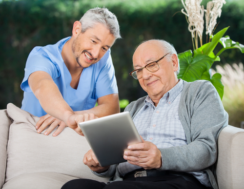 A care giver showing a senior citizen how to do something on an ipad - 3 Apps to Support Your Senior Loved One