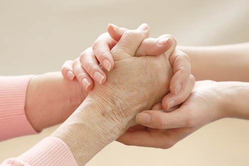 Four hands held in tandem, as a concept image for end of life care