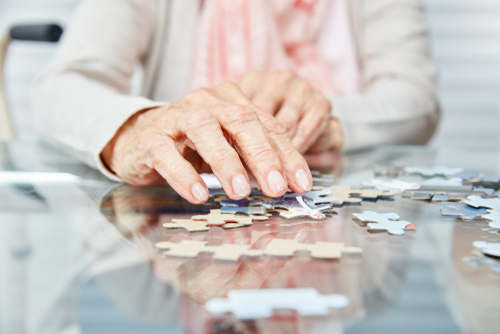 An old woman putting a puzzle together. - What is Sundowner's Syndrome?